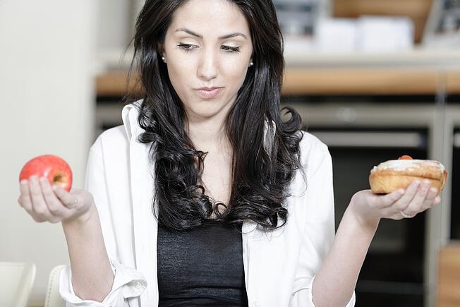 Attractive young woman choosing between a sticky cake or fresh fruit..jpeg
