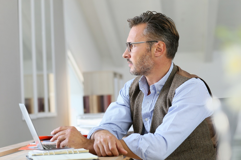Businessman at home looking away through window